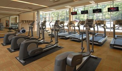 Rows of treadmills facing televisions with large screens