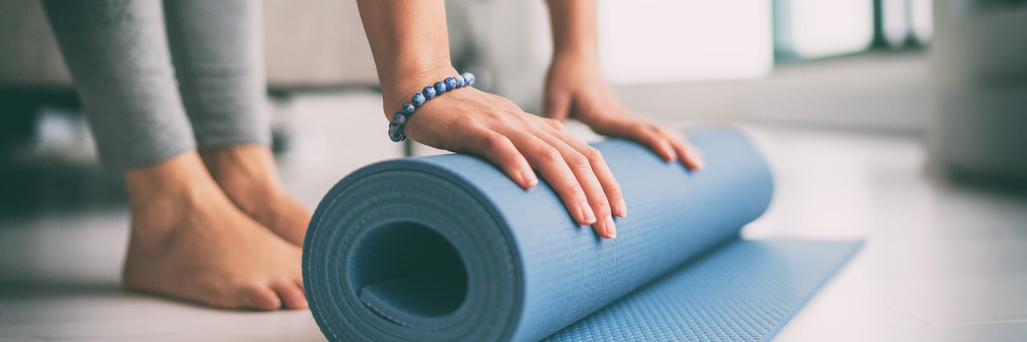 Woman unrolling her yoga mat